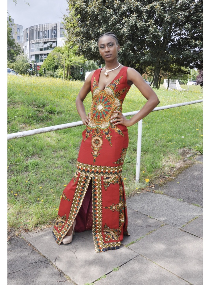 Full frontal of model wearing a red sleeveless fit and flare floor-length dress with African dashiki print. Also has slits to front and rear.