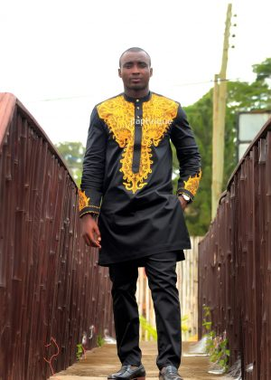 Full frontal of model wearing a solid black African senator suit with intricate gold embroidery on the neckline, chest, cuffs and back.