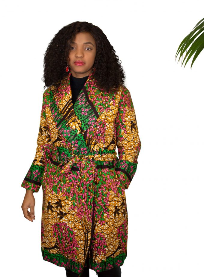 Full frontal of model wearing a golden belted trench coat in all over pink & green African floral print.