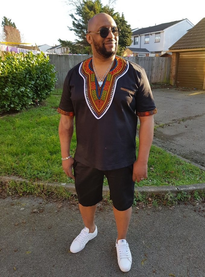Full frontal of model wearing a solid black short sleeve Dashiki shirt with black shorts.
