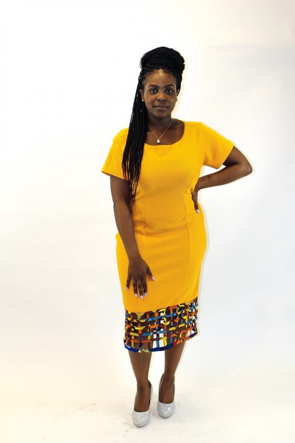 Frontal of model wearing a solid yellow bodycon dress with mesh detail on the hem.