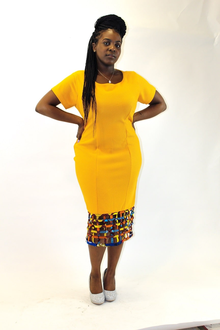 Frontal of model wearing a yellow bodycon dress with mesh hem detail in African print.