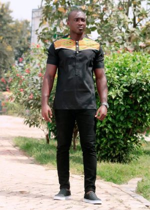 Full frontal of model wearing a solid black short sleeve shirt with vibrant multi-coloured Kente print across and above the chest to the neckline.