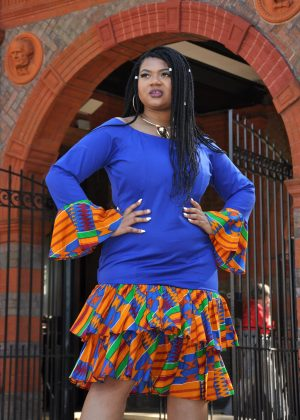Full frontal of model wearing a long sleeved blue bodycon dress with a layered ruffle hem in colourful African print.