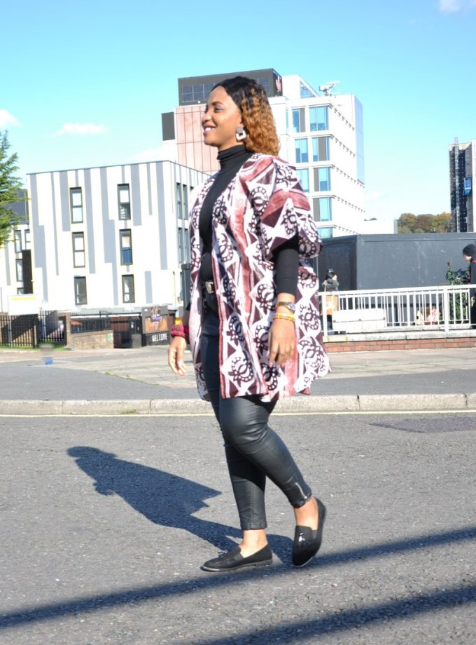 Full side shot of model wearing a brown ladies kimono style coat with open front and all over African batik print with a graphic geometric patter.