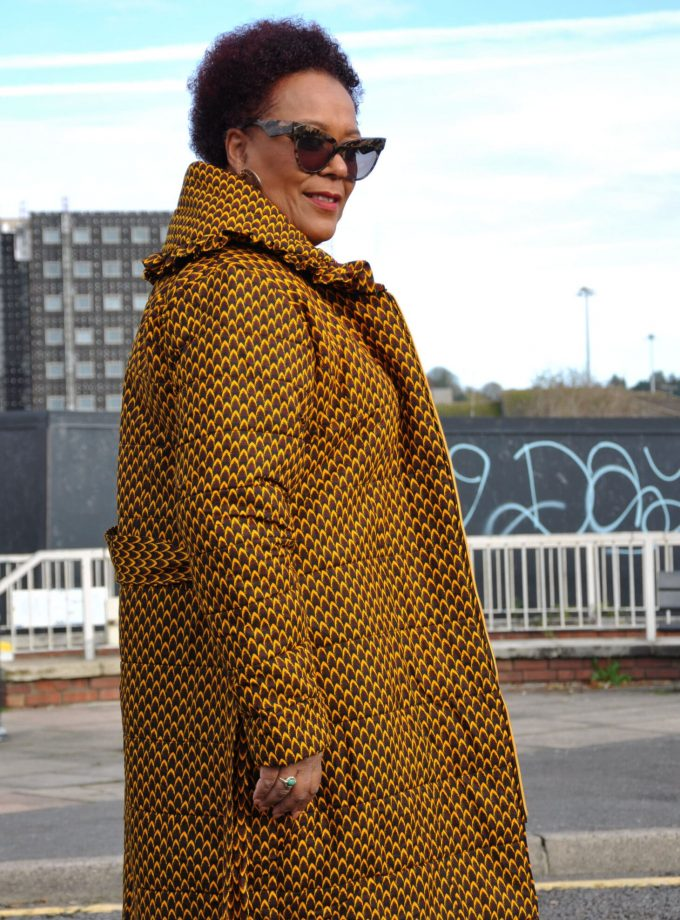 Side shot of model wearing a brown belted quilted ladies coat in all over African print.