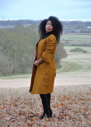 Side shot of model wearing a ladies mustard yellow ruffle sleeve belted trench coat in all over brown African print.