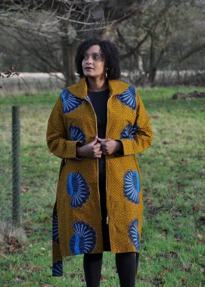 Full frontal of model wearing a mustard yellow African print trench coat with zipper.