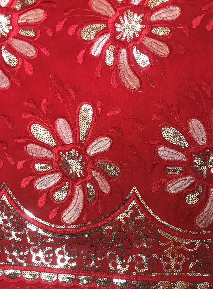 Close up of red Nigerian Geroge lace with gold embellishment.