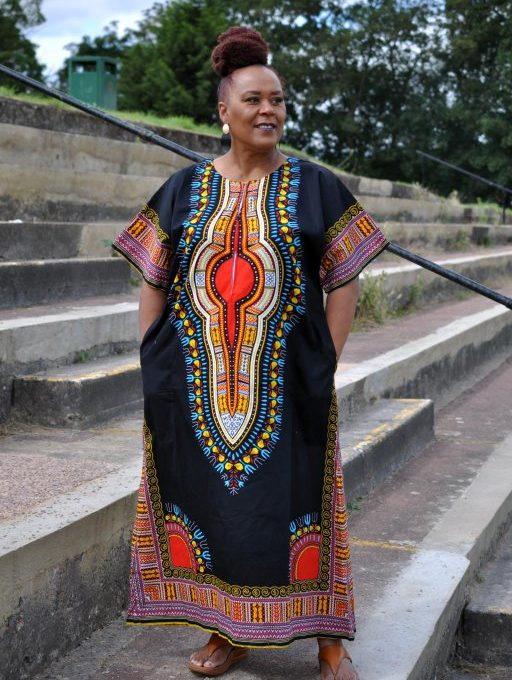 Full frontal of model wearing a black & multi-coloured dashiki print kaftan dress in maxi length.