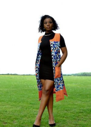 Full frontal of model wearing a ladies open front trench vest in all over colourful African print.