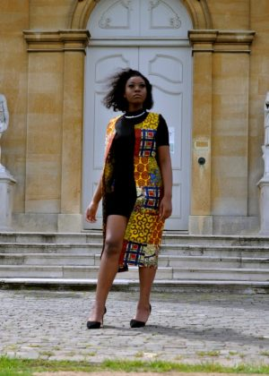 Full frontal of model wearing a colourful open front trench vest in all over African print.