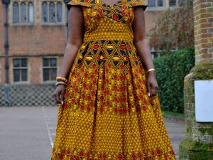 Full Frontal of model wearing a cap sleeve long a-line dress with full flounce skirt. Features all over vibrant African print.