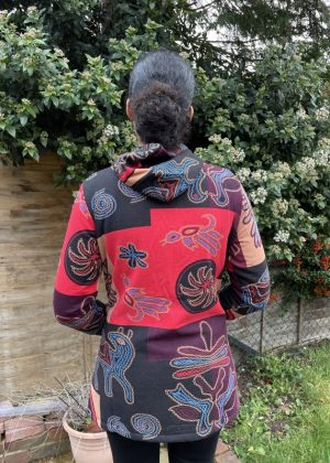 Back shot of model wearing a ladies hooded sports jacket in all over pink and purple patchwork and floral print pattern.