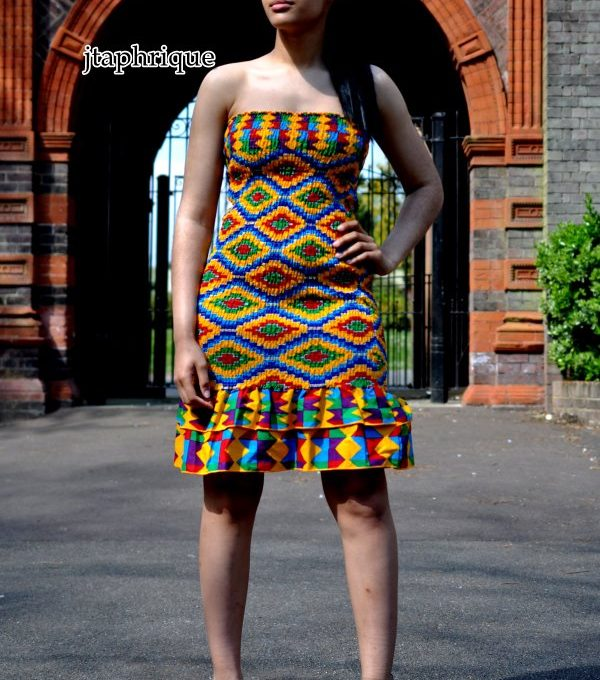 Full frontal of model wearing a shirred bodycon bandeau knee length dress in vibrant all over African print.