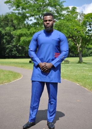 Full frontal of model wearing a solid blue African men's suit with a red 3 stripe pattern and buttons on left front side.