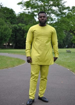 Full frontal of model wearing a custom made solid chartreuse yellow African men's suit with embroidery detail on chest in matching colour.