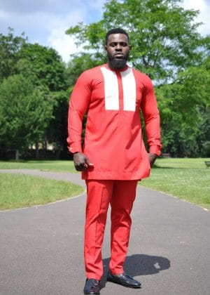 Full frontal of model wearing a custom made solid red men's African suit with two white vertical embroidery panels on the chest.