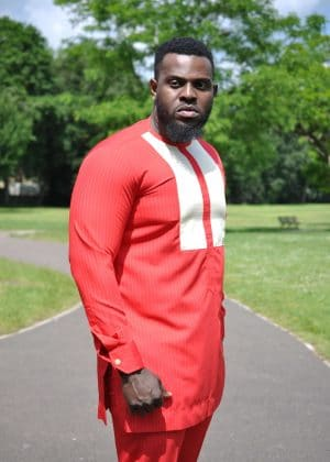 Close side shot of model wearing a solid red custom made African suit top with a round neckline and white embroidery detail on the chest.