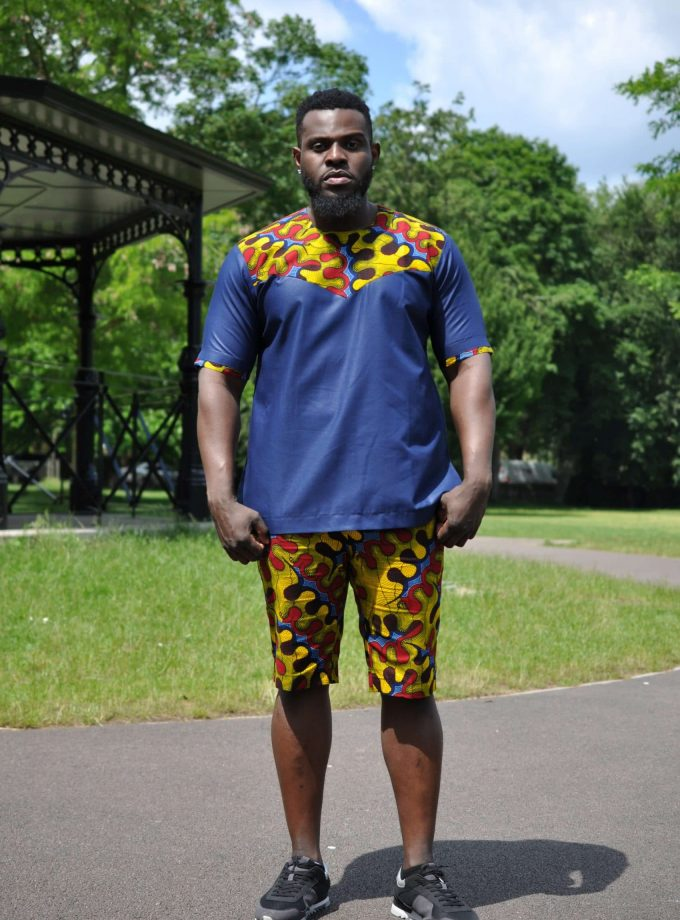 Azure Blue & African Print Short Pants Matching Set / Co-ord from African Clothing Store. SKU: 19259. Dark blue short sleeved shirt with round neckline and colourful African print in a banner across the of the upper chest over the shoulders to the upper back. Shorts are in matching colourful print and there is a strip of the same print on the sleeve hem.