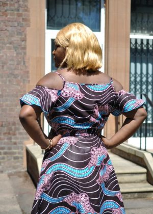 Back close shot of model showing the spaghetti strap and cold shoulder design of this African print dress