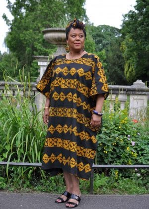 Full frontal of model wearing a black kaftan maxi dress with butterfly pattern all over in saffron yellow tie dye.
