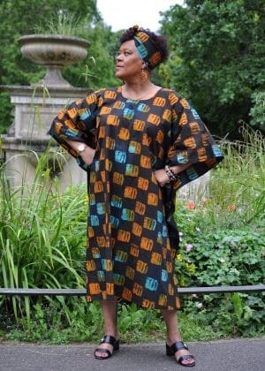 Full frontal of model wearing a black kaftan maxi dress with all over checker tie dye print in mostly orange but some blue.