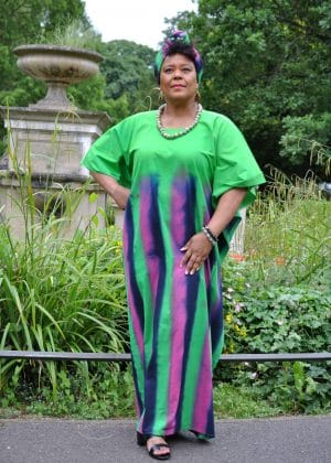 Full frontal of model wearing a long green kaftan dress with pink and blue vertical stripes from chest downwards.