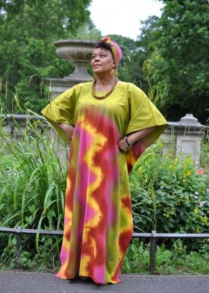 Full frontal of model wearing a long, lime green kaftan dress with vibrant colourful swirly tie dye print on the front and back.