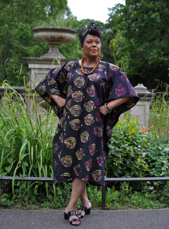 Full frontal of model wearing a black kaftan maxi dress with all over gold tie dye pattern.