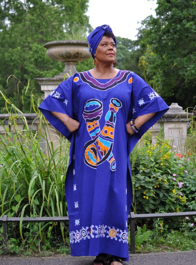 Full frontal of model wearing a ling cobalt blue kaftan dress in tie dye print.