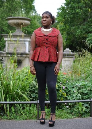 Full frontal of model wearing a sleeveless red peplum top with Peter Pan collar.