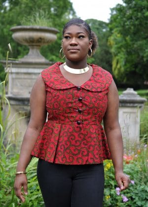 Close frontal of model wearing a sleeveless red peplum top with gold swirly African print all over.