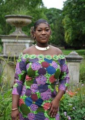 Close front shot of model wearing a colourful lace trim African print fit and flare dress with all over colourful cube and dice print.