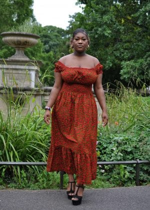 Full frontal of model wearing a red and gold African print maxi dress with shirred waist and all over swirly print.