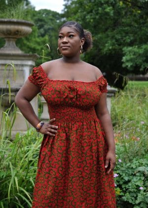Close frontal of model wearing a red and gold African print maxi dress with square neckline that can convert to an off shoulder look.