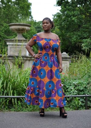 Full frontal of model wearing a colourful ruffle hem cap sleeve maxi dress in all-over African circle print.