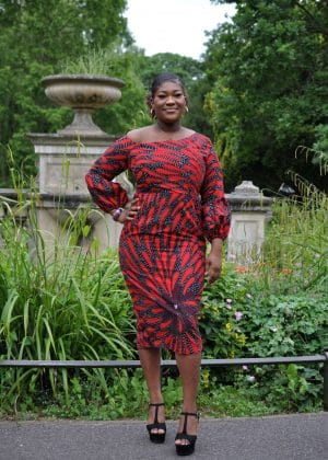 Full frontal of model wearing a custom made long sleeved red and black bodycon midi dress in all over African print.