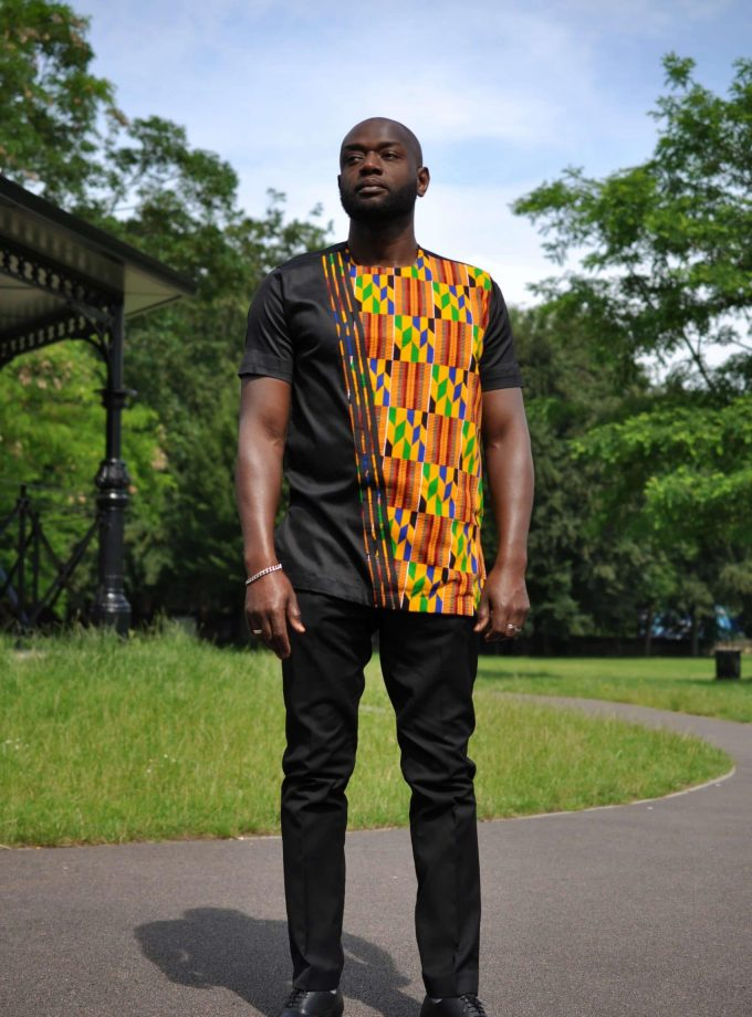 Full frontal of model wearing a solid black short sleeve shirt with African Kente print on front left of shirt.