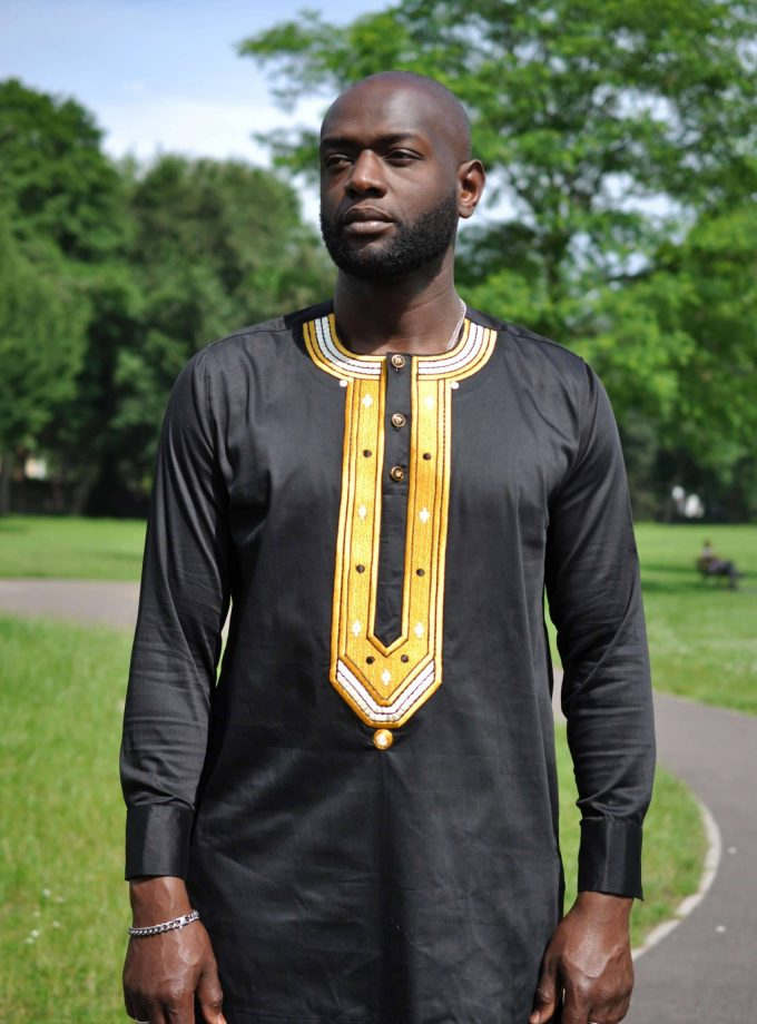 Close frontal of model wearing a solid black men's African shirt with a gold embroidery panel on the chest.