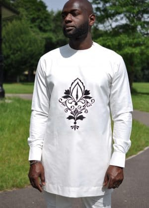 Close frontal of model wearing a solid cream men's African suit with a dark flower print image on the front.