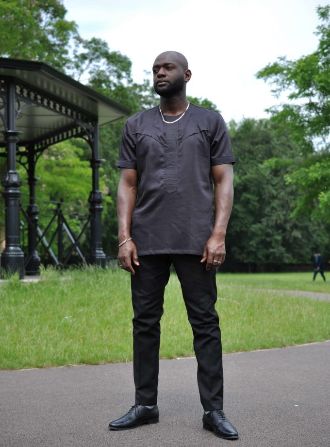 Full frontal of model wearing a solid black short sleeve African shirt with a simple embroidery design on the chest.