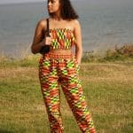 Full frontal of model wearing a bandeau crop top and matching joggers in colourful African print.