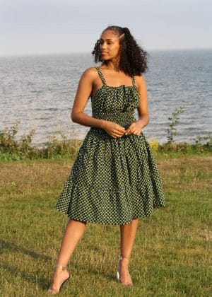 Full frontal of model wearing a dark green cotton a-line strap summer dress in subtle, intricate white and yellow african print.