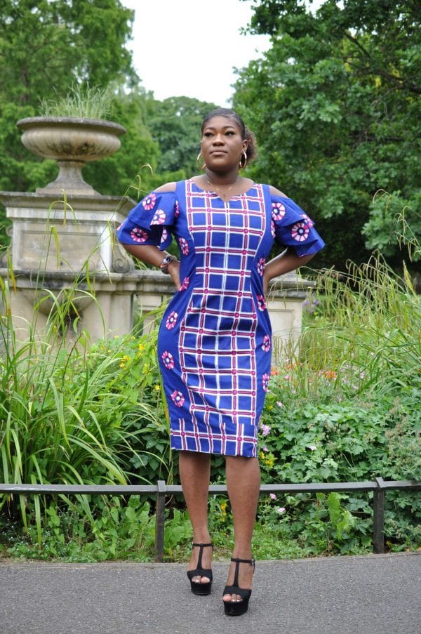 Full frontal of model wearing a blue custom made African midi dress with a mixed geometric African print pattern.