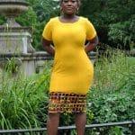 Full frontal of model wearing a solid yellow short sleeve bodycon midi dress with African Ankara print mesh hem.