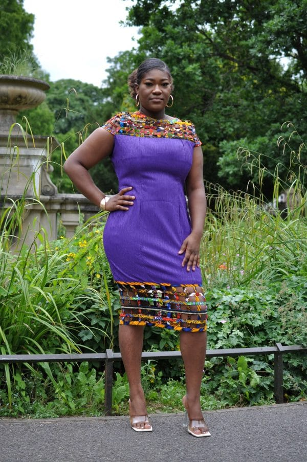 Full frontal of model wearing a solid indigo purple bodycon dress with mesh detail on the neckline and hem in multi-coloured African print.