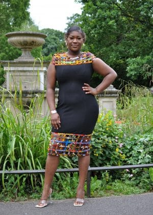 Full frontal of model wearing a solid black bodycon dress with mesh detail on the neckline and hem in multi-coloured African print.