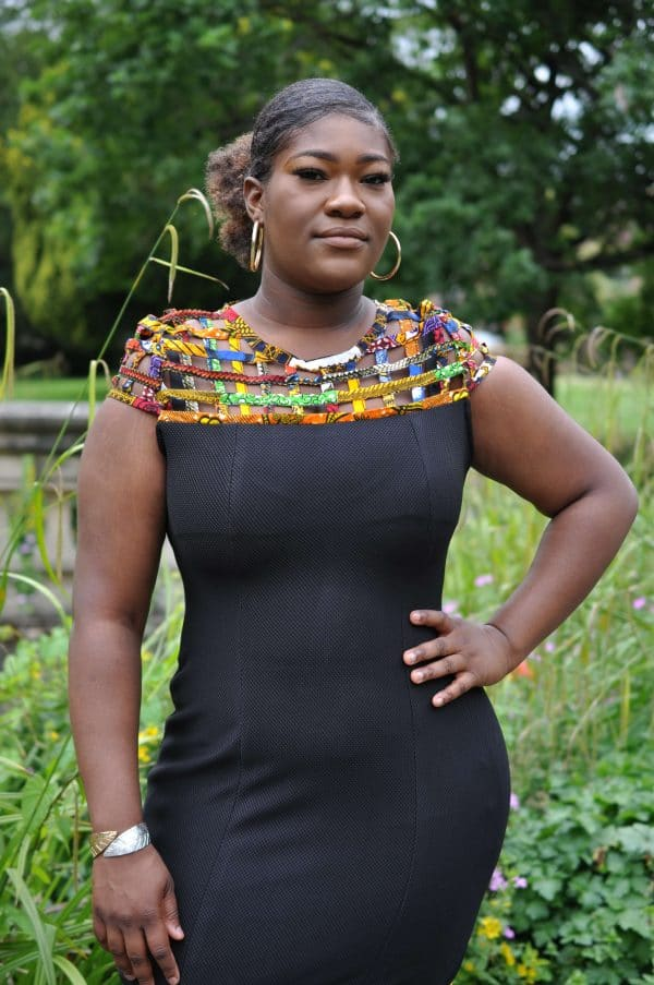 Close frontal of model wearing a solid black bodycon dress with colourful African print mesh detail on the neckline.