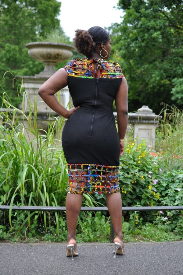 Back shot of model wearing a black bodycon dress with African print mesh detail.